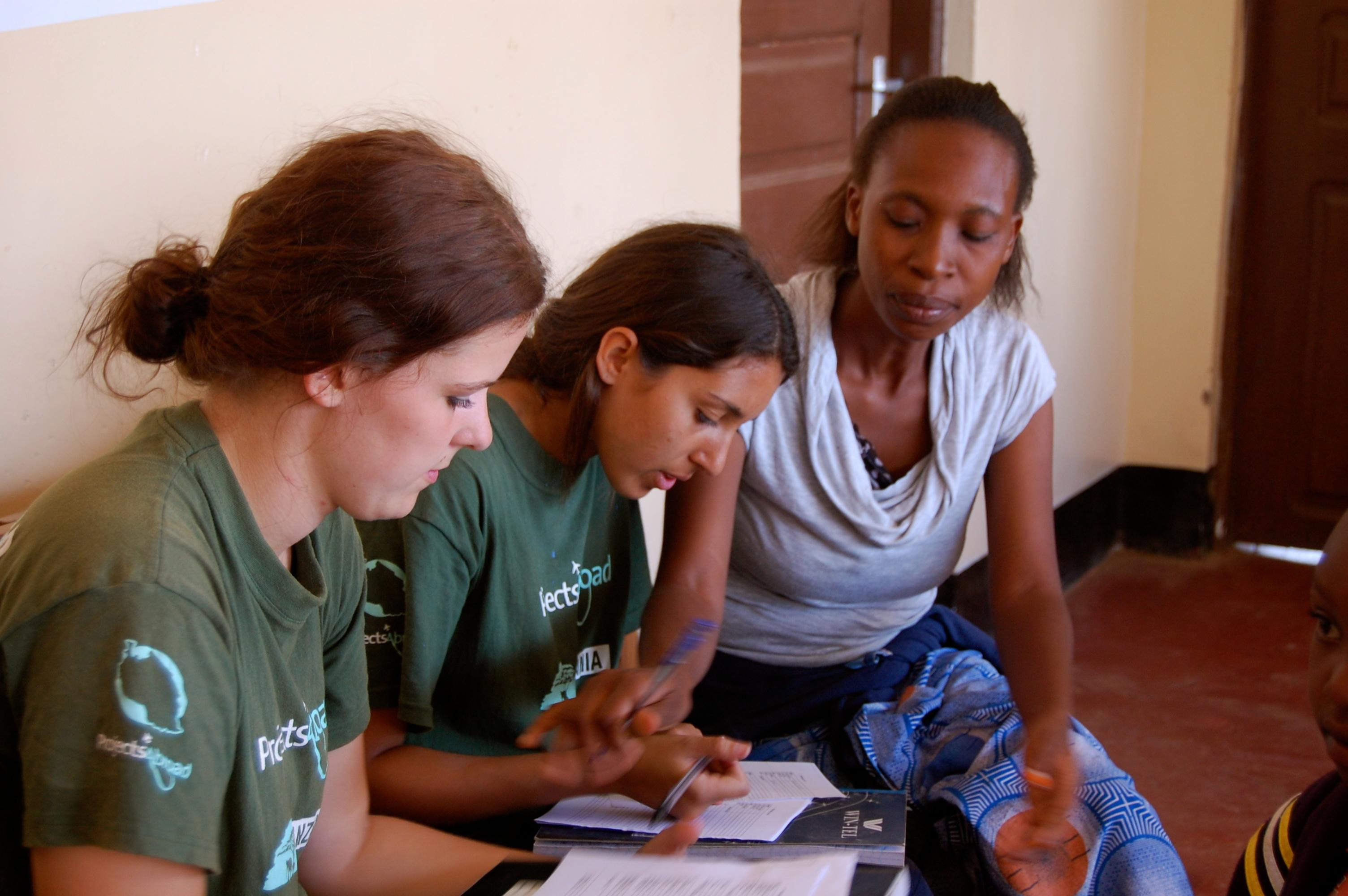 Interns with Projects Abroad helping a local lady fill out a medical note during their time on a occupational therpay internship in Tanzania.